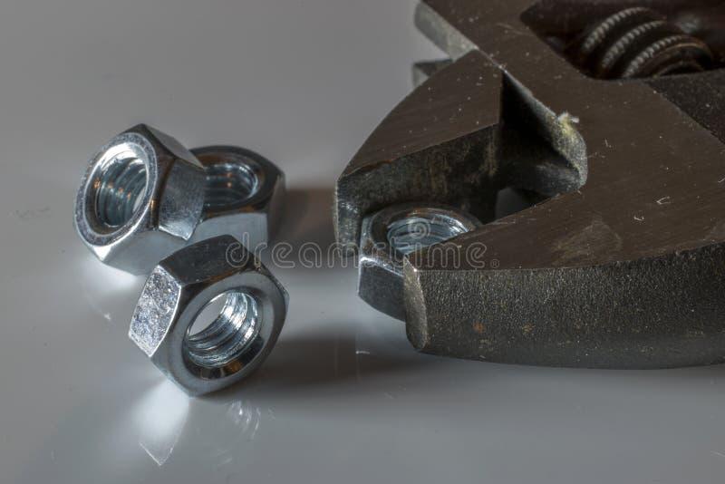 Nueces y llave de acero con el fondo blanco imágenes de archivo libres de regalías