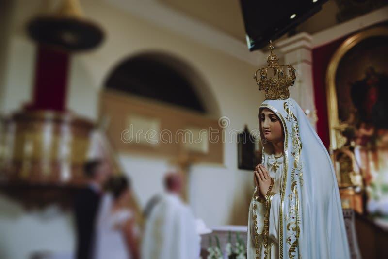 Nuestra señora bendice a los recienes casados en la iglesia fotos de archivo