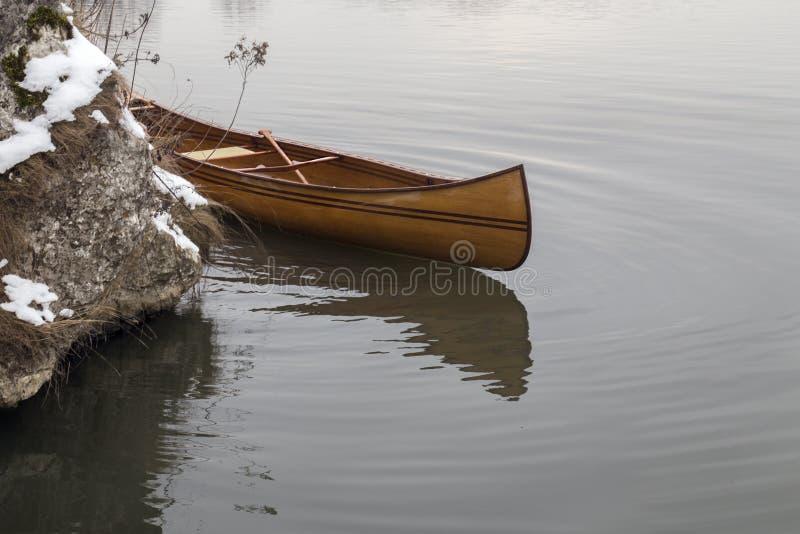 Nueva canoa que flota en el agua tranquila en puesta del sol del invierno imagen de archivo libre de regalías