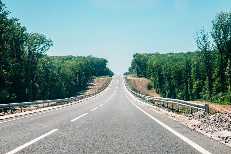 Nueva carretera de asfalto con el emplazamiento de la obra del borde de la carretera en la reconstrucción de la carretera de asfa fotos de archivo