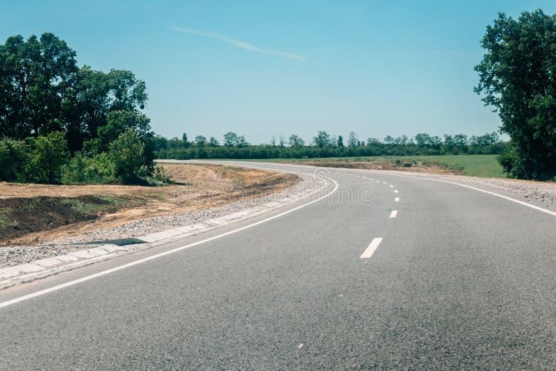 Nueva carretera de asfalto con el emplazamiento de la obra del borde de la carretera en la reconstrucción de la carretera de asfa foto de archivo
