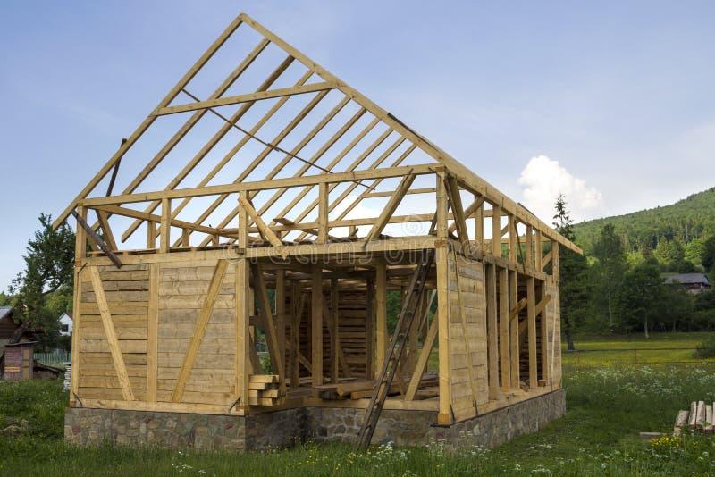 Nueva casa de madera bajo construcción en vecindad rural reservada Marco de madera de los materiales naturales para las paredes y imagenes de archivo