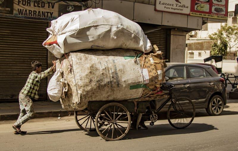 Nueva Delhi, India, 19 de febrero de 2018: Hombre cargando carga masiva en bicicleta imagen de archivo libre de regalías