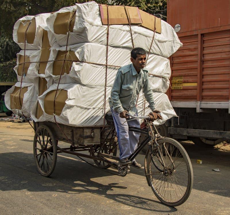 Nueva Delhi, India, 19 de febrero de 2018: Hombre cargando carga masiva en bicicleta imagen de archivo