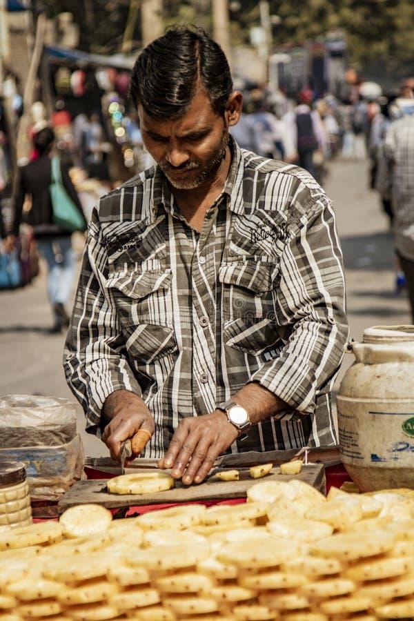 Nueva Delhi, India, 19 de febrero de 2018: Hombre prepara piña para la venta en un carro callejero imágenes de archivo libres de regalías