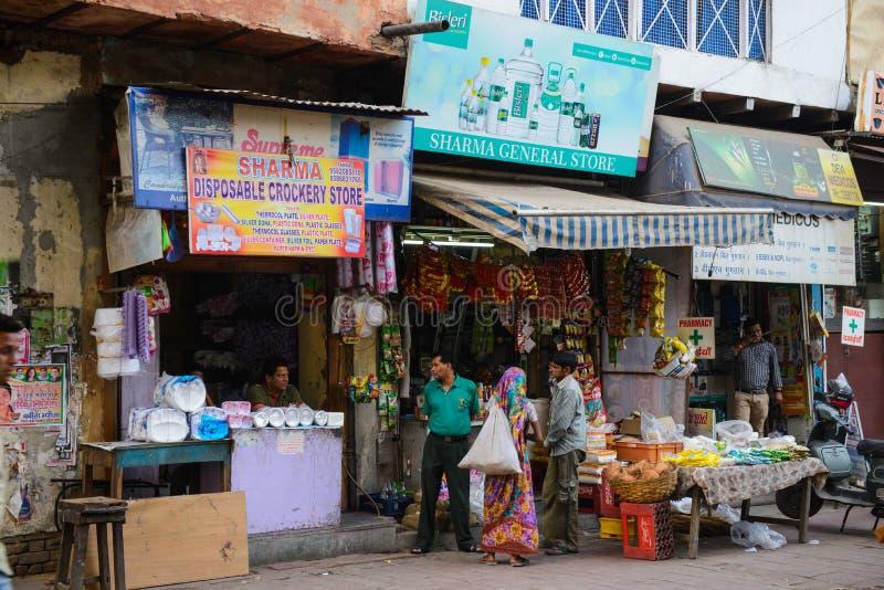 Nueva Deli, la India - 10 de abril de 2016: Gente no identificada en el aire libre de la pequeña tienda al por menor con las frut imagenes de archivo