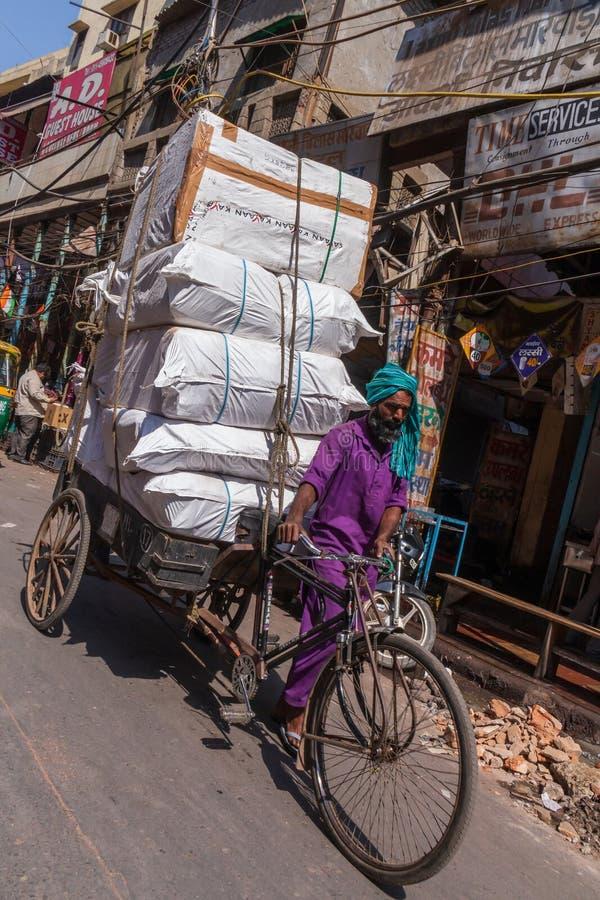 NUEVA DELI, LA INDIA - 13 DE MARZO DE 2018: hindú con el vehículo que entrega el cargo foto de archivo libre de regalías