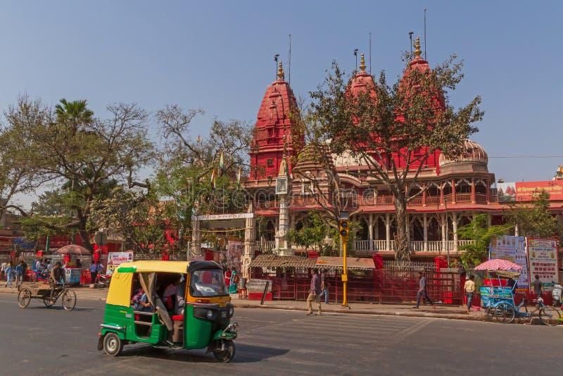 NUEVA DELI, LA INDIA - 13 DE MARZO DE 2018: tuk-tuk en la calle delante del templo imagen de archivo libre de regalías
