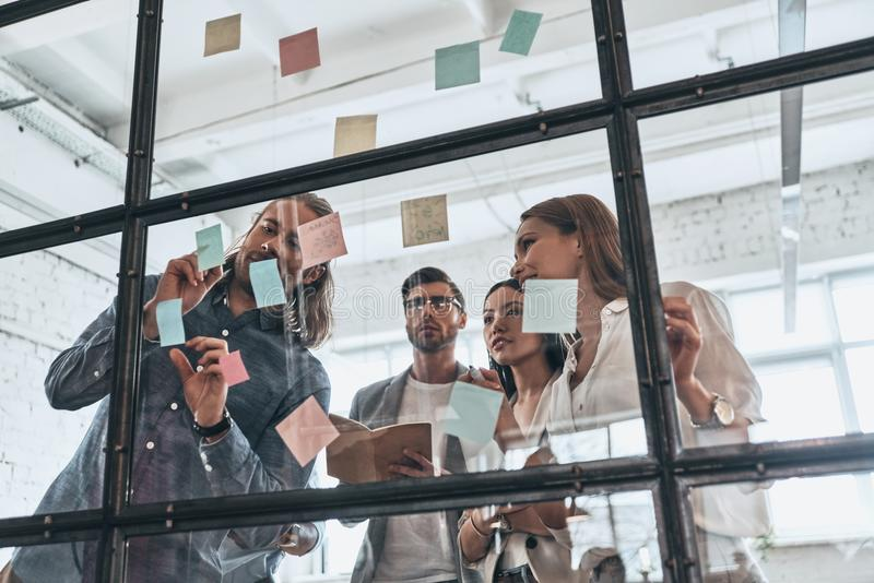 Nueva estrategia que se convierte Grupo de gente moderna joven en c elegante imagen de archivo libre de regalías
