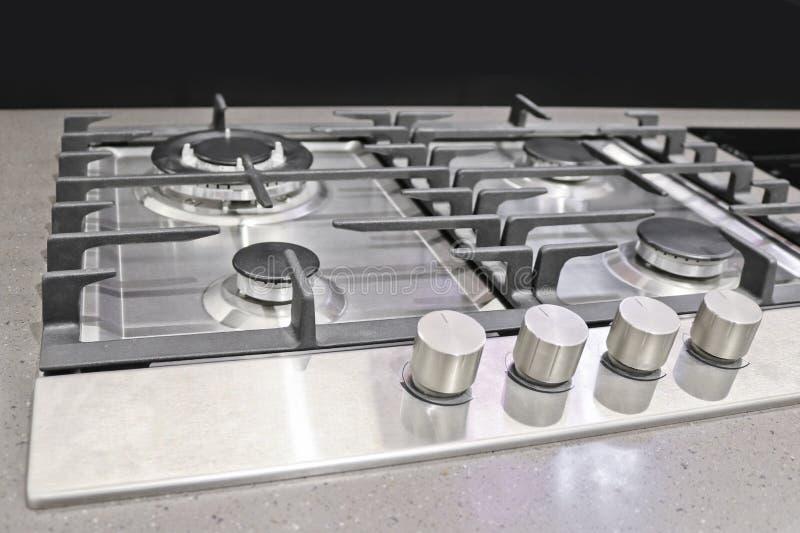 Nueva estufa de gas moderna con cuatro hornillas para la cocina, superficie de acero inoxidable imagen de archivo libre de regalías