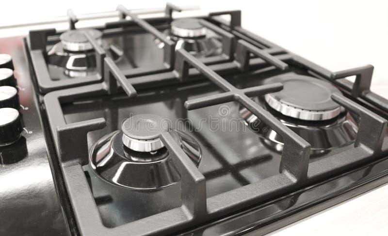 Nueva estufa de gas moderna con cuatro hornillas para la cocina, superficie esmaltada negra fotografía de archivo libre de regalías