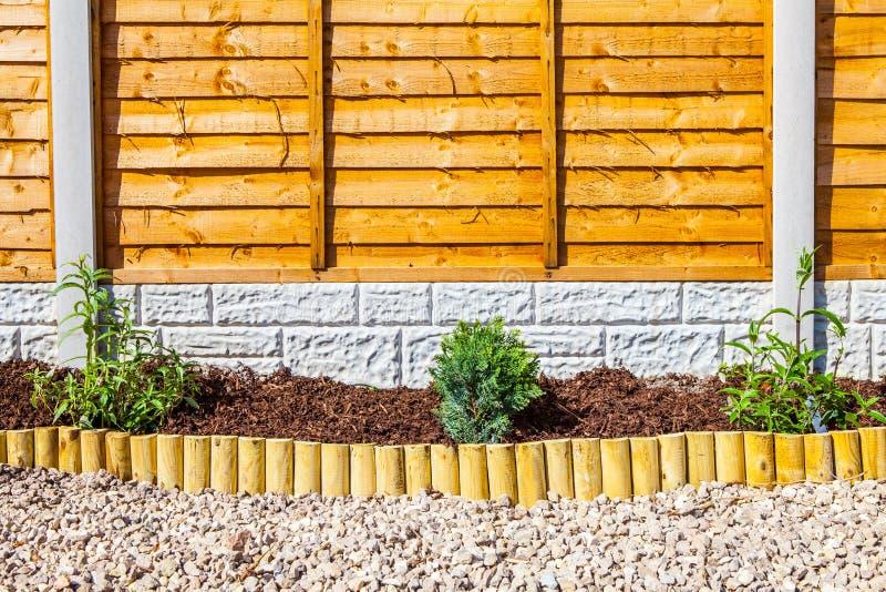 Nueva frontera ajardinada del jardín del pedazo de madera foto de archivo