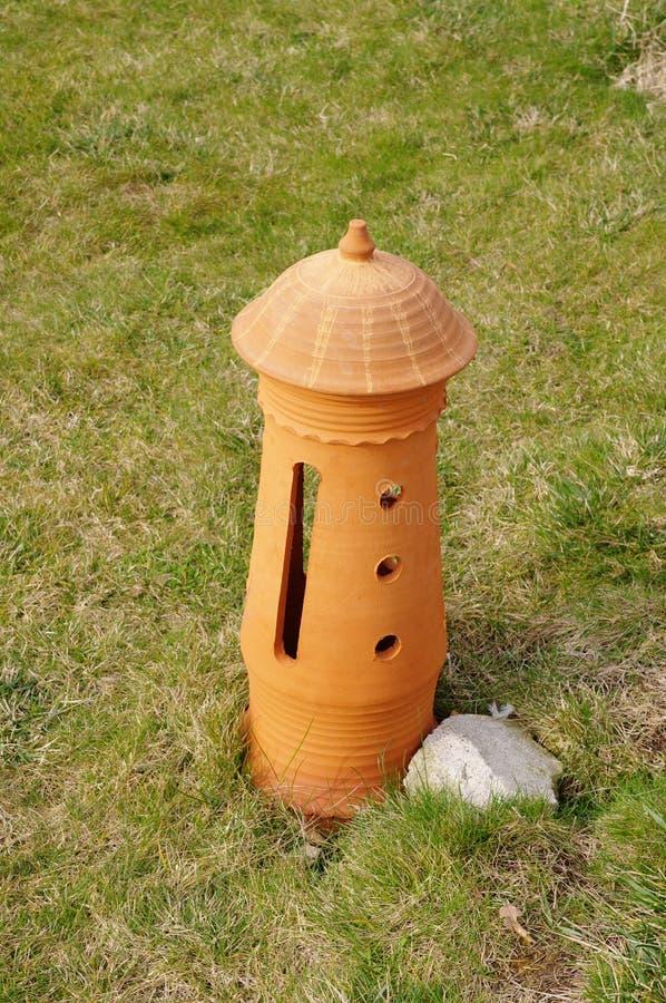 Nueva lámpara de la terracota en la hierba fotografía de archivo