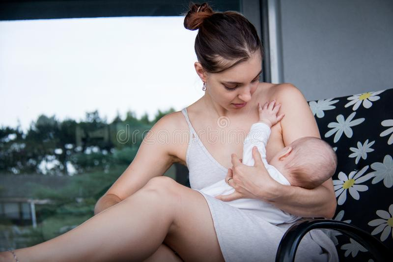 Nueva mamá que detiene a su pequeño hijo y que amamanta, bebé de cuidado imagenes de archivo