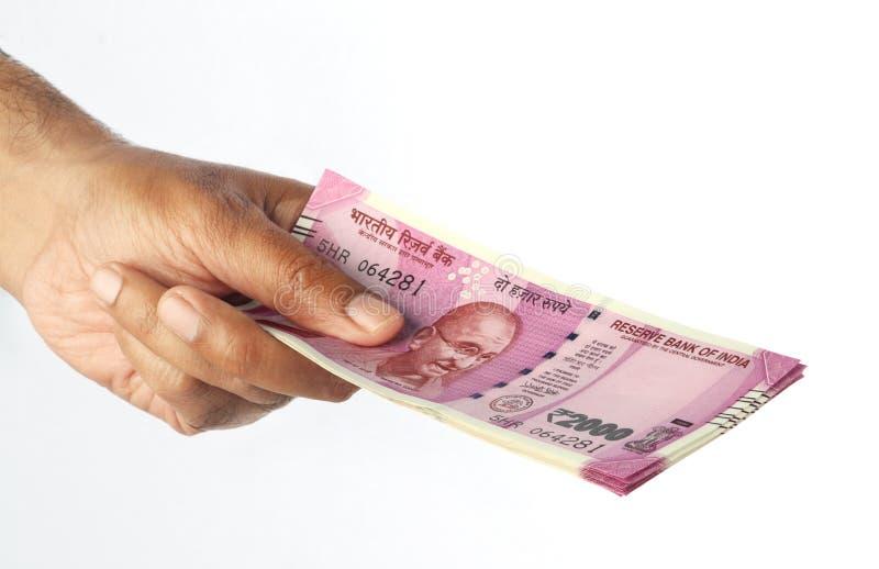 Nueva nota 2000 de la moneda de la rupia india en una mano en blanco foto de archivo
