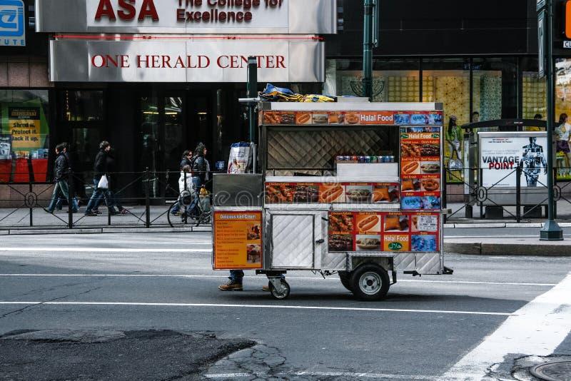 Nueva York, los E Febrero de 2009 soporte del perrito caliente que cruza una avenida de Manhattan foto de archivo