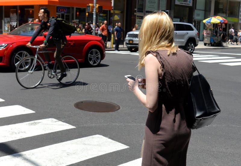 Nueva York, los E.E.U.U. - 30 de mayo de 2018: Uso de la mujer su smartphone en el st fotografía de archivo