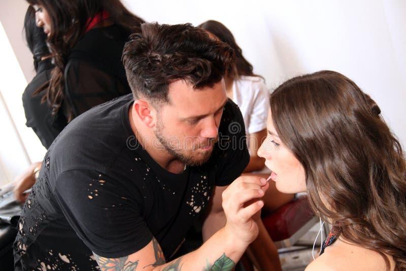 NUEVA YORK, NY - 16 de junio: Un artista de maquillaje que aplica maquillaje a la cara modelo entre bastidores foto de archivo libre de regalías