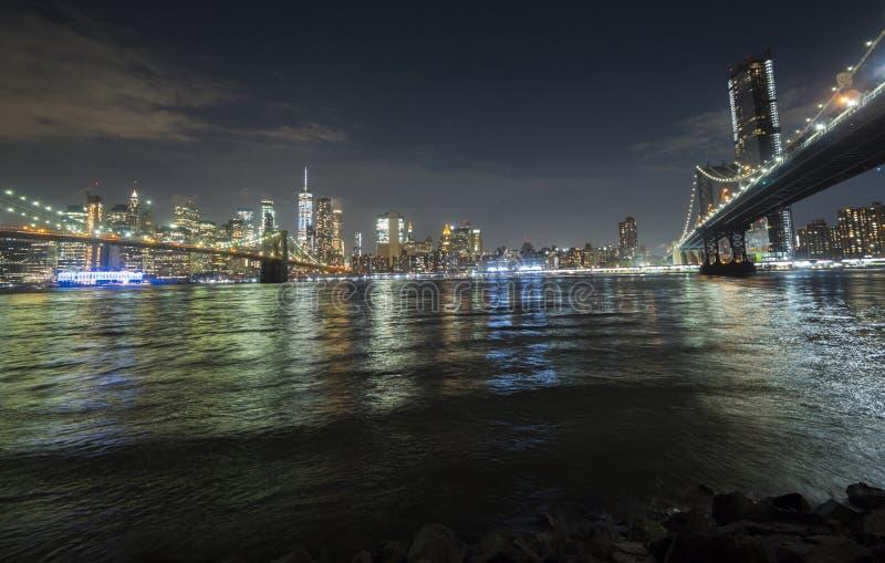Nueva York por noche y dos puentes en el primero plano - puente de Brooklyn y puente de Manhattan fotografía de archivo