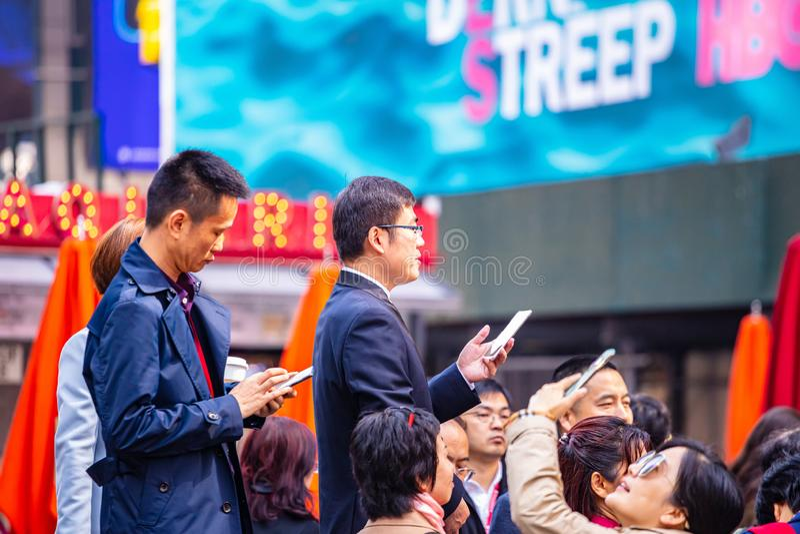 Nueva York, Times Square Grupo de personas que sostiene los teléfonos móviles, fondo colorido de los anuncios, día de primavera s imágenes de archivo libres de regalías