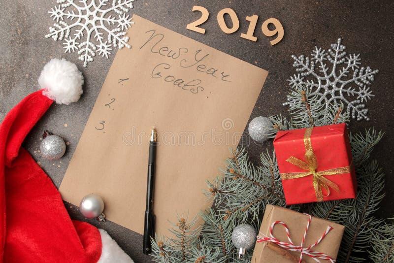 Nuevas metas 2019 Texto en un trozo de papel con una pluma y la decoración del Año Nuevo en un fondo oscuro fotos de archivo libres de regalías