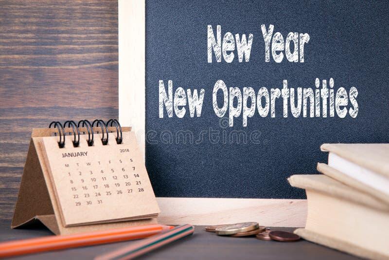 Nuevas oportunidades del Año Nuevo calendario y pizarra de papel en una tabla de madera fotos de archivo