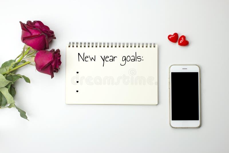 Nuevas palabras de las metas del year' s en el cuaderno con las rosas y el teléfono elegante imagen de archivo
