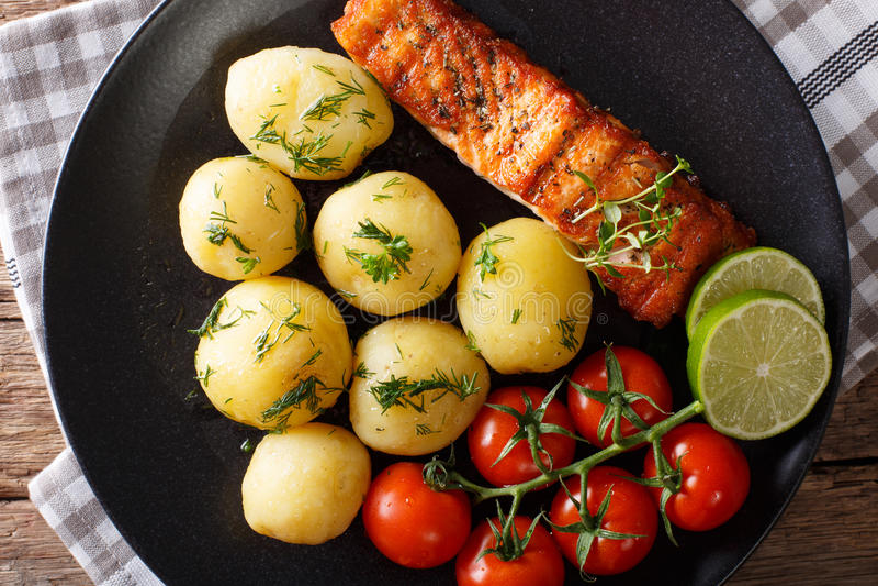 Nuevas patatas de color salmón y hervidas asadas a la parrilla con la mantequilla, clo de los tomates foto de archivo