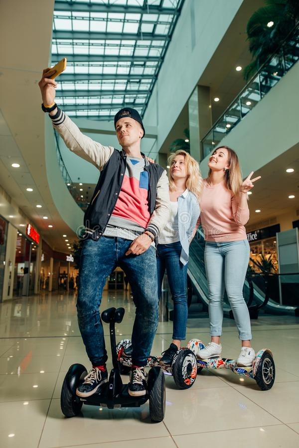 Nuevas tecnologías modernas tres personas en el hoverboard que hace el selfie imágenes de archivo libres de regalías