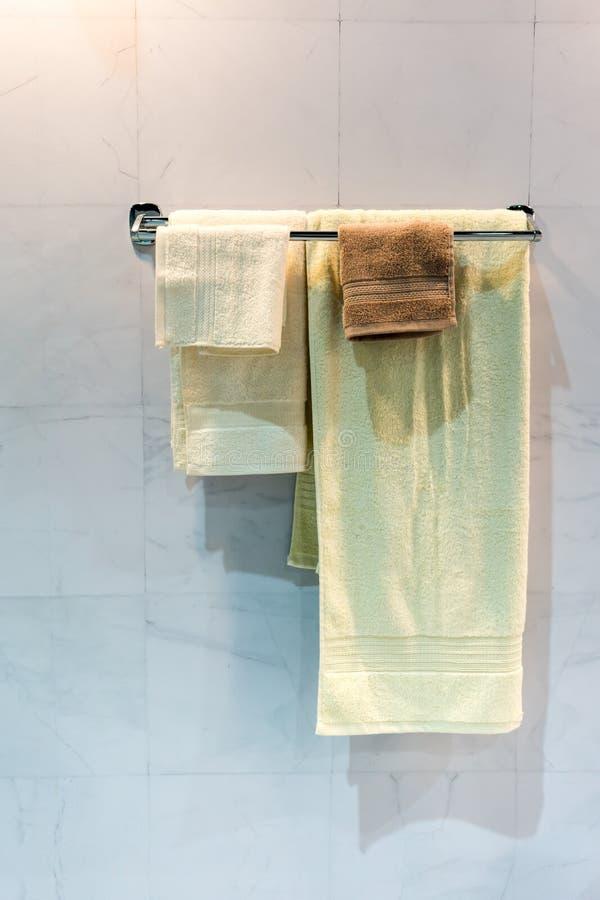 Nuevas toallas dobladas amarillas y marrones que cuelgan en el carril del metal bajo l foto de archivo libre de regalías