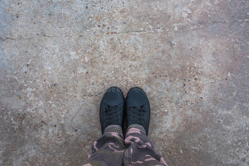 Nuevas zapatillas de deporte modernas en superficie de la acera concreta imagen de archivo libre de regalías