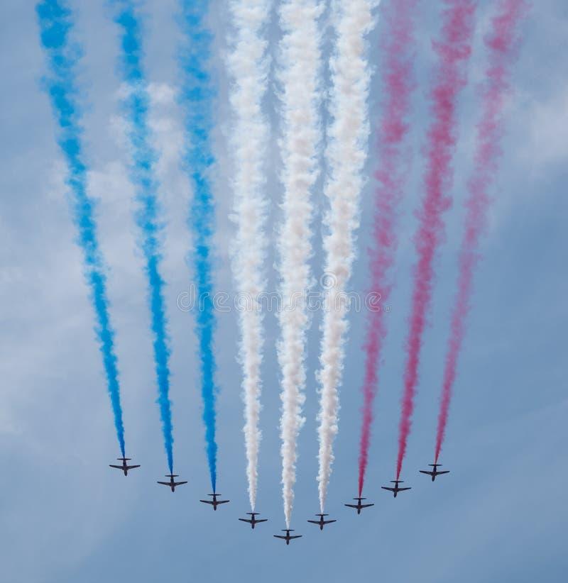 Nueve aviones rojos de las flechas vuelan en rastros blancos de la formación y azules rojos de emisión del humo en la marcha el d fotos de archivo libres de regalías