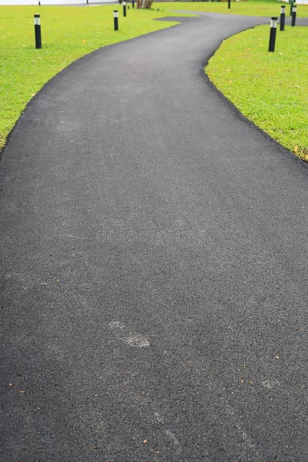 Nuevo asfalto que es suavemente calzada del camino en el jardín de la hierba verde fotos de archivo libres de regalías