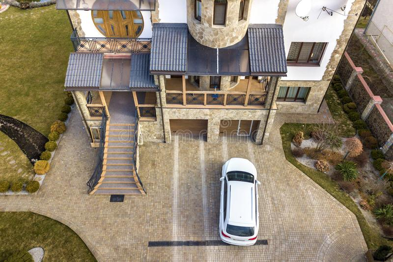 Nuevo blanco aparcamiento en calzada pavimentada con el césped verde, los arbustos decorativos y la cerca del ladrillo de la casa imagenes de archivo
