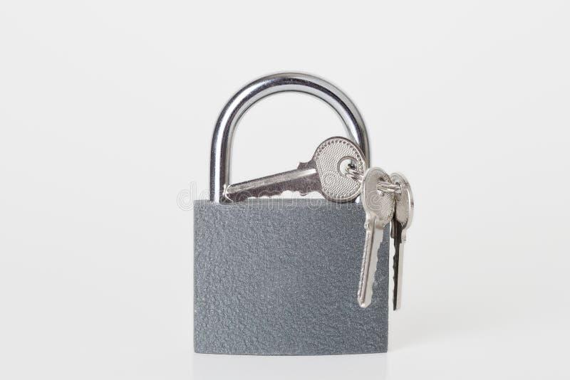 Nuevo candado gris con llaves en el fondo blanco foto de archivo