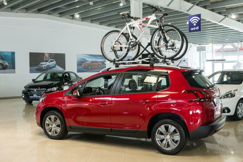 Nuevo coche familiar rojo Peugeot 2008 con un soporte en el tejado para las bicicletas en la concesi?n de coche imagenes de archivo