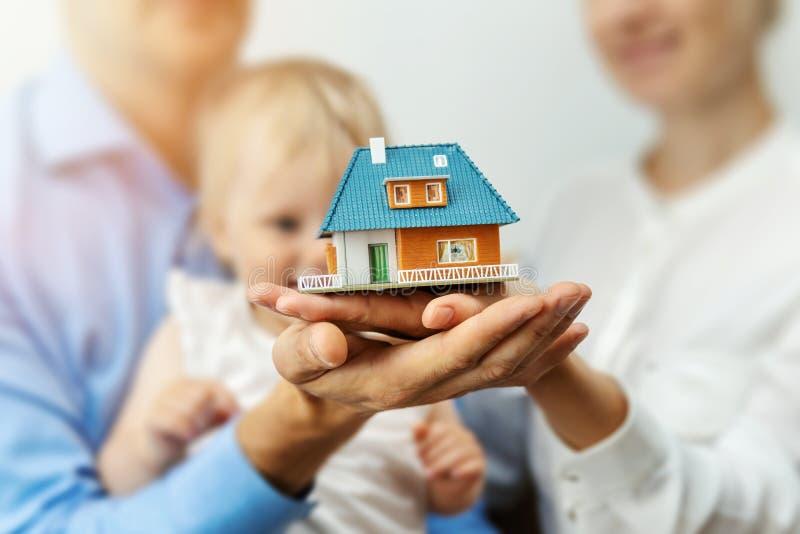 Nuevo concepto casero - familia joven con el modelo de escala de la casa ideal foto de archivo