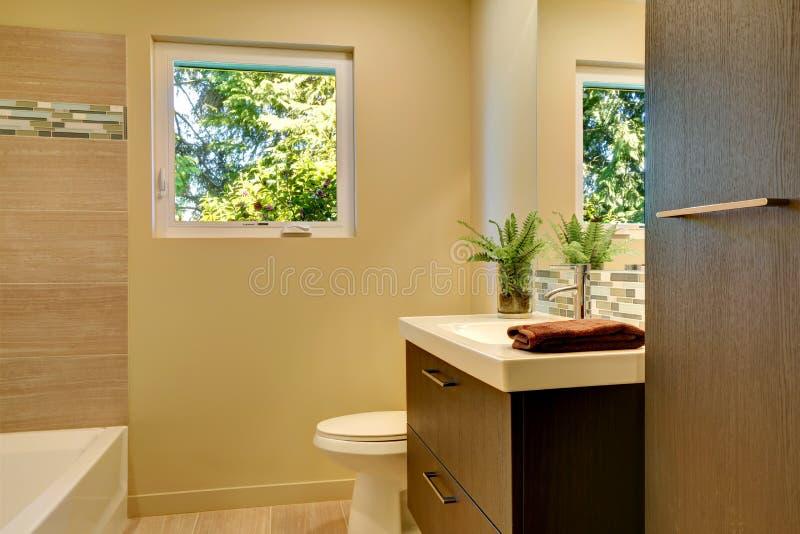 Nuevo cuarto de ba o moderno beige con los gabinetes y la tina de madera marrones imagen de - Lo ultimo en cuartos de bano ...