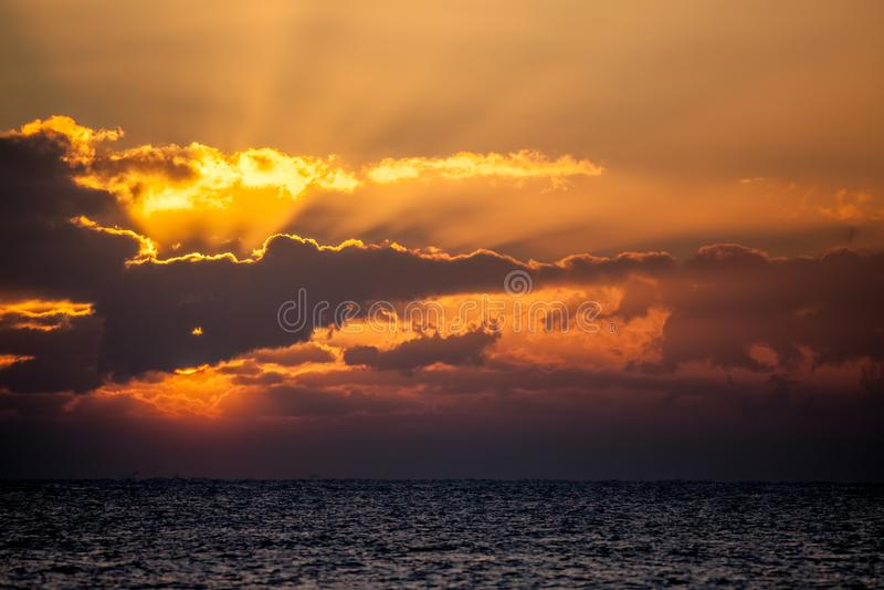 Nuevo día Horizonte del amanecer del océano con el sol que se rompe detrás de la nube foto de archivo