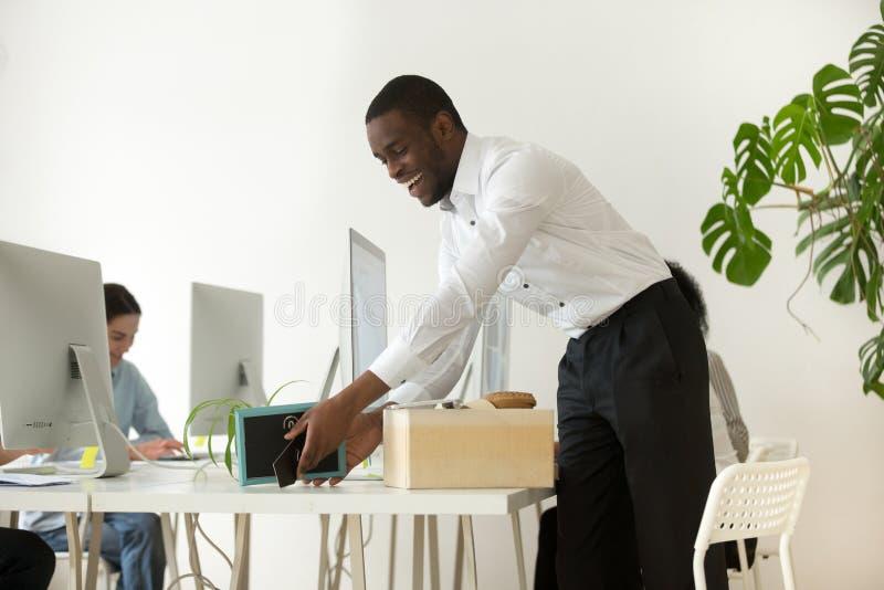 Nuevo empleado africano feliz que desempaqueta pertenencia en el primer trabajo foto de archivo