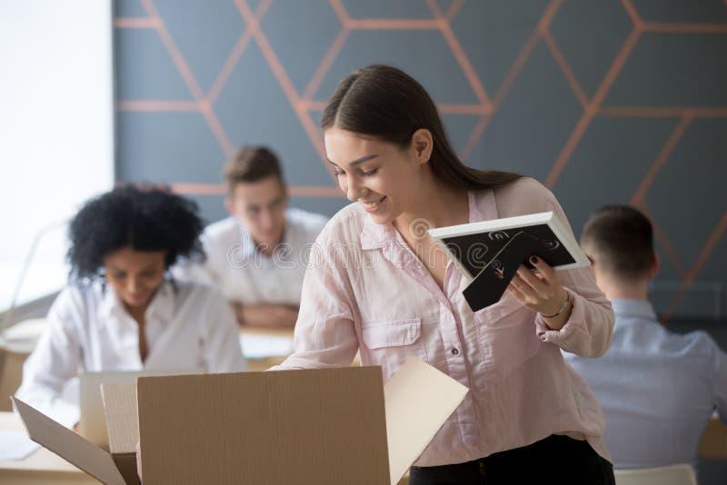Nuevo empleado de sexo femenino sonriente que desempaqueta la caja en el lugar de trabajo en oficina imagen de archivo
