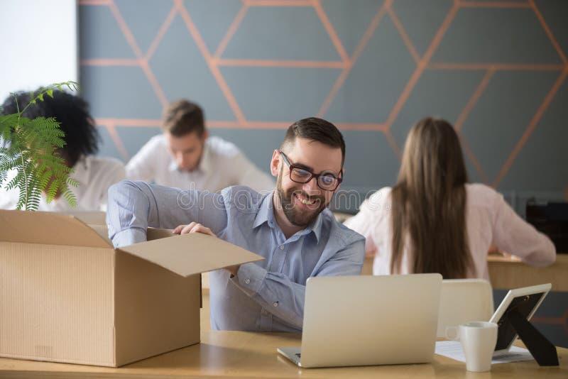 Nuevo empleado de sexo masculino milenario sonriente que desempaqueta la caja en el wor de la oficina fotos de archivo