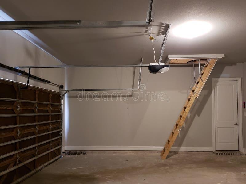 Nuevo garaje con la escalera de madera de la puerta al ático en una nueva casa imagen de archivo