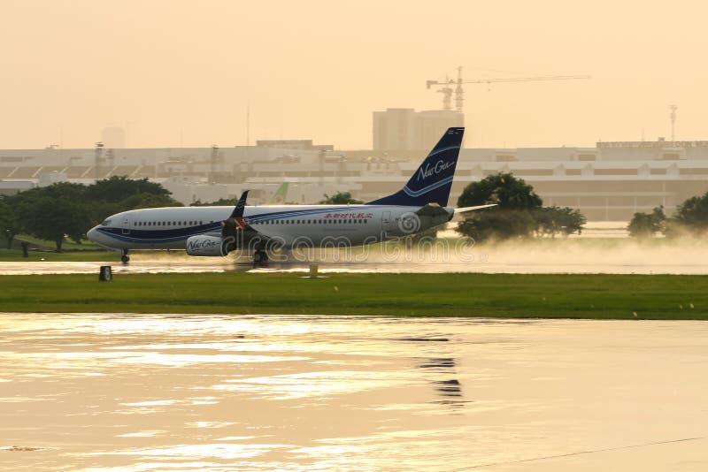 Nuevo Gen Airways Boeing 737, registro HS-NGH, nombrado Fang Wang, saca de una pista mojada del aeropuerto internacional de Donmu fotografía de archivo libre de regalías