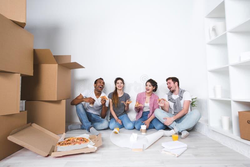 Nuevo hogar Amigos que se sientan en el piso en el nuevo apartamento y que comen la pizza después de desempaquetar imágenes de archivo libres de regalías