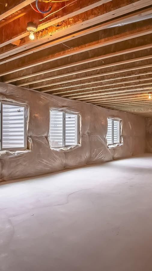 Nuevo hogar del marco vertical bajo construcción con las ventanas instaladas en la pared cubierta plástica fotografía de archivo libre de regalías