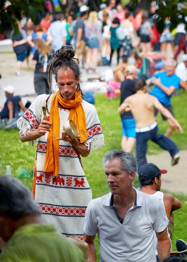 Nuevo hombre joven del hippie de la edad que juega sonidos con una amoladora del mortero y de la maja en el festival de los tams  foto de archivo