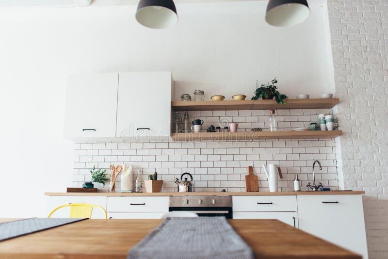 Nuevo interior ligero moderno de la cocina con los muebles y la mesa de comedor blancos fotos de archivo libres de regalías