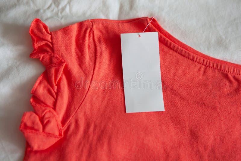 Nuevo niño rosado o la camiseta de las mujeres con la etiqueta en el fondo blanco Compras del concepto, ventas del verano, descue imagenes de archivo