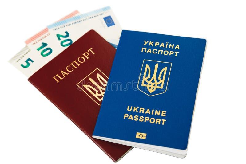 Nuevo pasaporte biométrico internacional azul ucraniano que miente en pasaporte internacional rojo ucraniano viejo con efectivo e foto de archivo